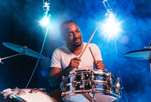 Young African-american Jazz Musician Or Drummer Playing Drums On Blue Studio Background In Glowing Smoke Around Him. Concept Of Music, Hobby, Inspirness. Colorful Portrait Of Joyful Attractive Artist.