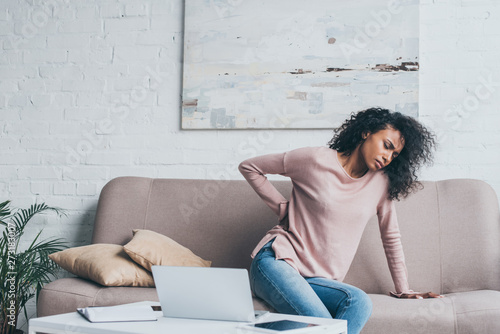 Fotografía unhappy african american woman suffering from back pain while sitting on sofa ne