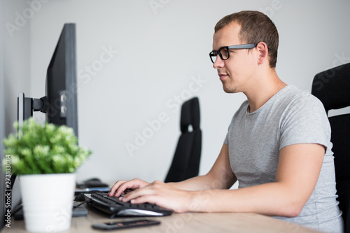 Valokuva  portrait of young handsome man using computer in office or home