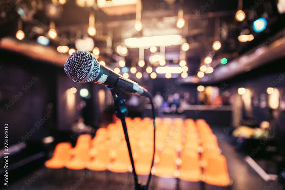 Fototapeta Empty event hall: Close up of microphone stand, empty seats in the blurry background