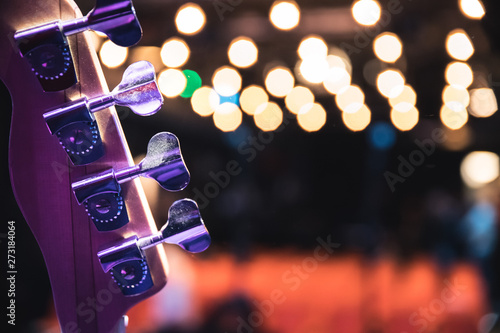 Concert flair: Close up of guitar neck, empty seats and lights in the blurry background - 273184064