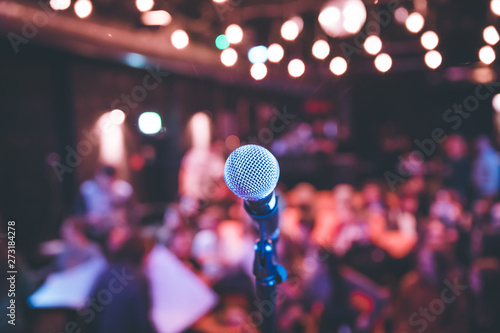 Event hall: Close up of microphone stand, seats with audience in the blurry background - 273184278