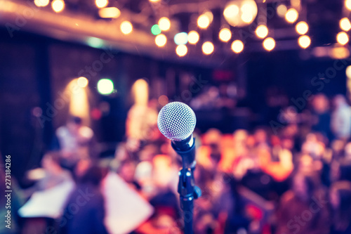 Event hall: Close up of microphone stand, seats with audience in the blurry background - 273184286