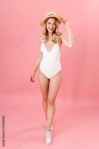 Fototapeta Happy young woman posing isolated over pink wall background dressed in swimwear