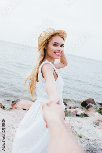 cropped view of man holding hands with happy blonde woman in straw hat