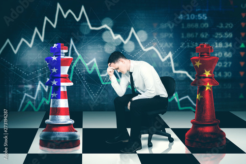 Valokuva  Young businessman looks stressed with trade war