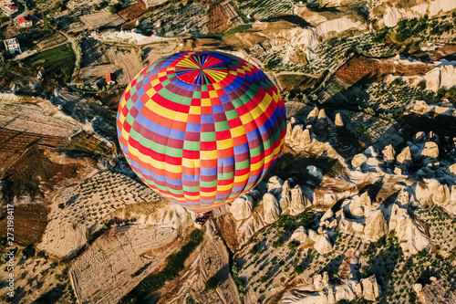 Photo Goreme, Turkey - June 14, 2019: Travelers and tourists flying over mountains at sunset in a colorful aerostat balloon in Goreme, the Turkish cappadocia