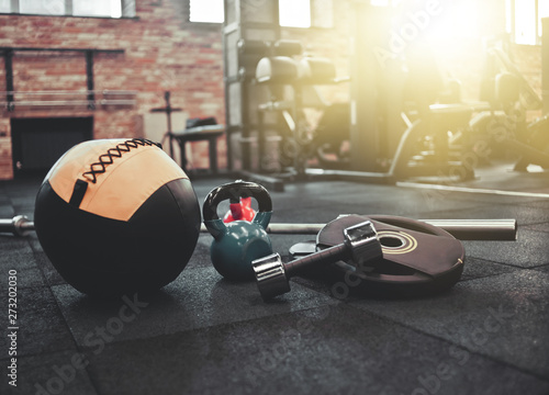 Fototapeta Disassembled barbell, medicine ball, kettlebell, dumbbell lying on floor in gym. Sports equipment for workout with free weight. Functional training obraz