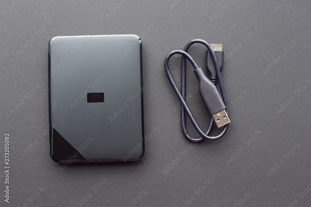 Fototapety, obrazy: External 1 TB hard drive with connecting cable on a gray background. Gadgets and computer accessories.