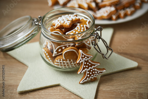 Foto Christmas gingerbread in a glass jar on a wooden table.