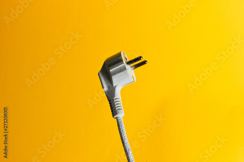 Fotomural  Electric plug closeup on yellow background
