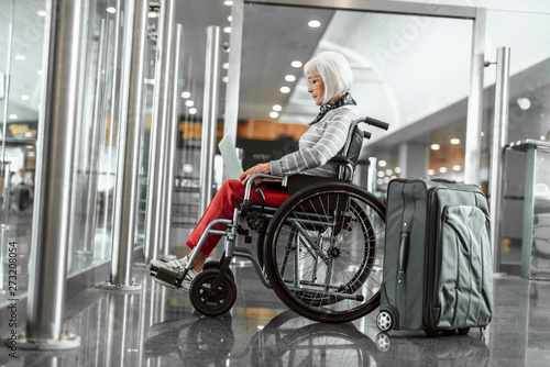 Spoed Fotobehang Retro Cheerful mature lady on disabled carriage working at laptop