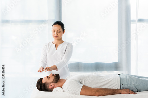 Photo  attractive healer putting hands above head while healing handsome bearded man