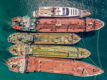 Aerial View Of Luxury Yacht Moored Up With Old Cargo Boats In The Mediterranean Sea, Nisi, Greece.