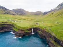 Aerial View Faraway Of M˙lafossur Waterfall Near A Small Village, Faroe Island.
