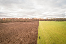 Aerial View Of A Man Standing Up At The Separation Between Two Different Colored Fields In Estonia.