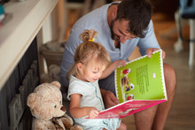 Father With Child Looking Picture Book