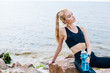 Leinwandbild Motiv blonde sportswoman holding sport bottle while sitting on stone near sea