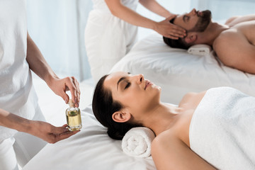 Fototapeta na wymiar selective focus of masseur holding bottle with oil near woman and man in spa center