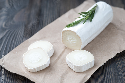 Fototapeta Fresh goat cheese with slices on paper. obraz