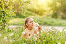 Girl Blowing At Dandelions