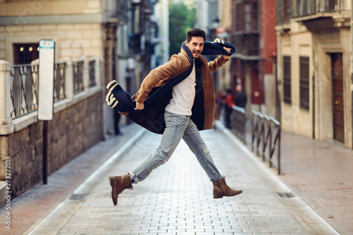 obraz dibond Young happy man jumping wearing winter clothes in urban background