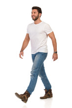 Smiling And Walking Man In White T-shirt, Jeans And Boots