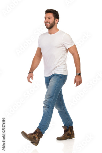 Fotomural  Smiling And Walking Man In White T-shirt, Jeans And Boots