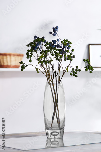 Foto op Canvas In het ijs A shot of an interior design. In the middle there is a composition with several blueberry twigs in a transparent oval waterglass. On the blurred background there is a wall shelf with photo frame.
