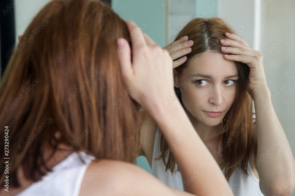 Fototapeta Portrait of a beautiful young woman examining her scalp and hair in front of the mirror, hair roots, color, grey hair, hair loss or dry scalp problem