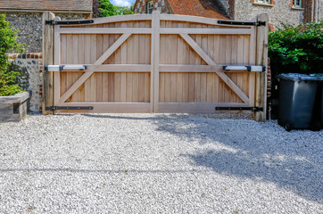 Large wooden entry electric gates with stone driveway.