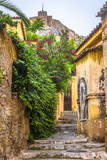 Fototapeta Na drzwi - Scenic narrow street with old houses in Plaka district, Athens, Greece. Plaka is one of the main tourist attractions of Athens. Vintage traditional alley overlooking the famous Acropolis of Athens.