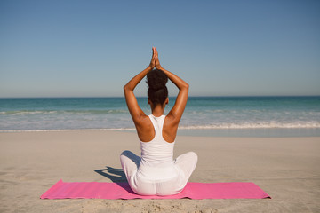 Woman doing yoga on exercise mat at beach in the sunshine