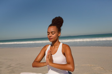 Woman doing yoga at beach in the sunshine