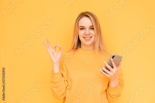Foto  Happy girl in bright clothes with a smartphone in her hand on a yellow background, shows an OK gesture with her fingers and looks into the camera