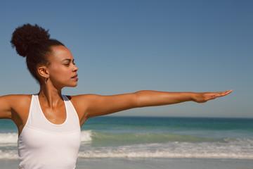 Beautiful woman doing yoga at beach in the sunshine