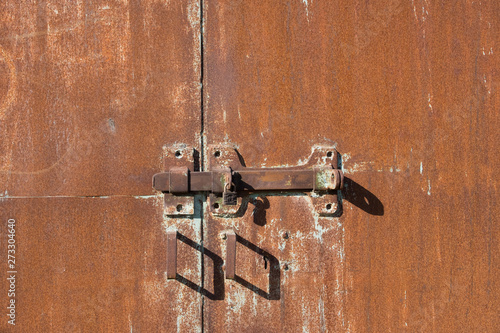 Background of old iron rusty gate. Metal gate with red rust. The texture of a rusty gate with a hinged and padlock lock. Gates with door handles.