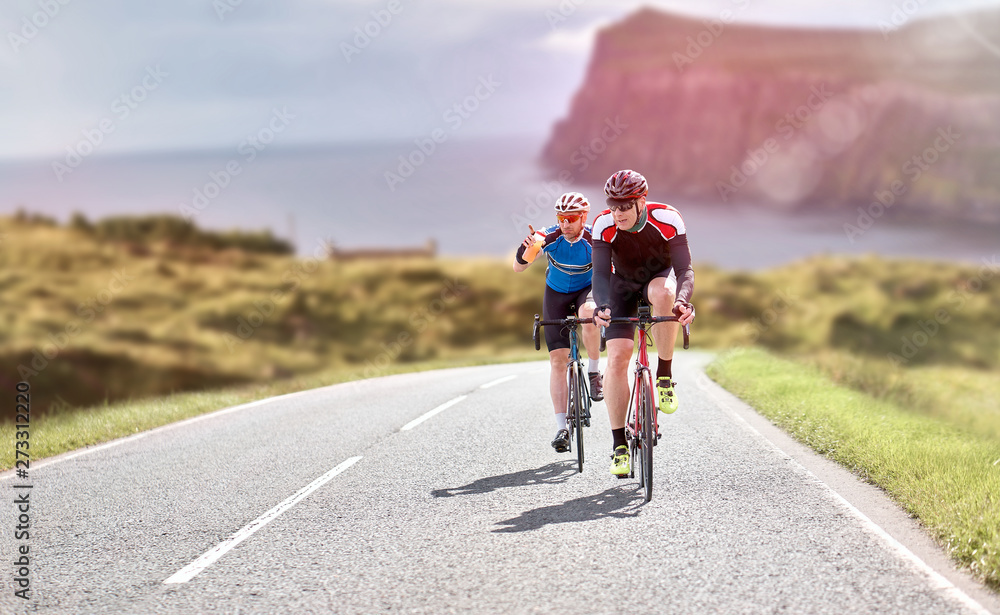 Fototapeta Cyclists out racing along country lanes near the coast in the United Kingdom