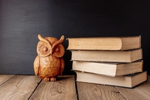 Back To School, The Concept Of Parenting. A Stack Of Books And A Statuette Of An Owl. A Day Of Knowledge. A Place For Text On A Blackboard. Save Space. Rustic And Vintage Toning.