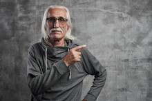 Aged Gray Haired Caucasian Man Points To The Side With Index Finger, Advertises Something. Grandfather In Glasses With Mustache Recommends Buying Your Product