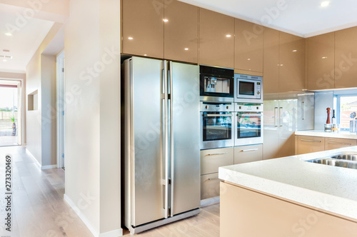 Photo  A modern refrigerator in the luxury kitchen with microwave ovens fixed to the wa