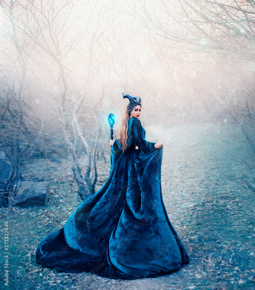 Fototapeta horned stranger in long emerald silk dress deep in forest alone with magic stick in hand, terrible vampire hiding from morning sunlight, demon daughter went down to ground to search for sinners