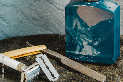 Blue aftershave bottle with old razor on wet stone texture Canvas Print