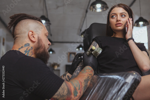 Photo Beautiful woman talking on her smart phone while getting tattooed by professional tattoo artist