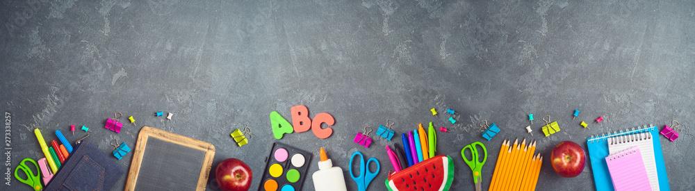 Fototapeta Back to school background with school supplies on blackboard.