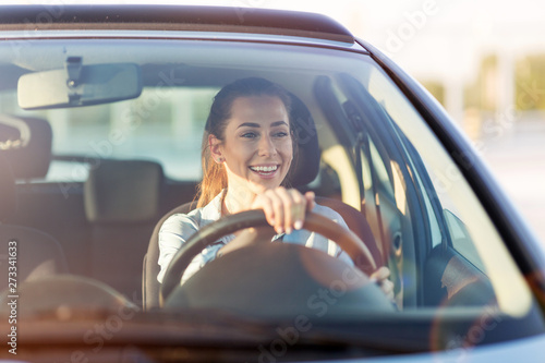 Fényképezés Happy woman driving a car and smiling