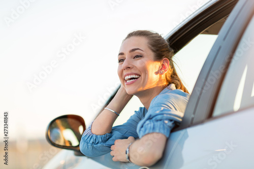 Fotografiet Happy woman driving a car and smiling