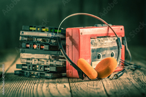 Closeup of cassette tape, red walkman and headphones - 273341850
