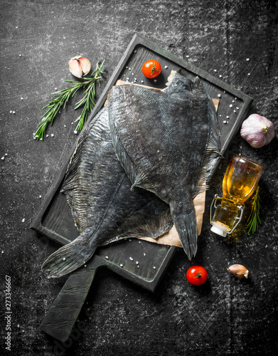 Fototapeta Fresh raw flounder on paper with rosemary.