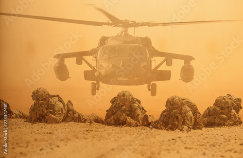 Foto Military soldiers in front of helicopter between storm and dust in battle field